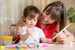 Mother and kid paint together at home Stock Photography