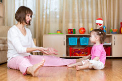 Mother and kid play with ball indoors Royalty Free Stock Images