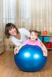 Mother and kid play with fitness ball indoors. Mother and kid girl play with fitness ball indoor Royalty Free Stock Photos