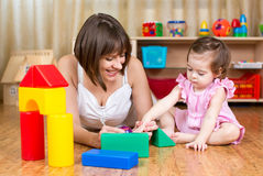 Mother and kid play toys indoors Stock Photos