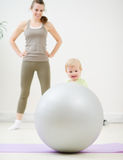Mother and kid playing with fitness ball. In gym Stock Images
