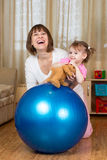 Mother and kid playing with fitness ball home. Mother and kid play with fitness ball play Royalty Free Stock Photo