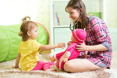 Mother with kid playing and treating doll Stock Image
