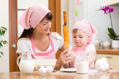Mother and kid preparing cookies together at kitchen Royalty Free Stock Images