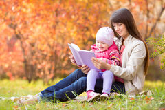 Mother and kid read a book outdoors in autumn Royalty Free Stock Photography