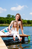 Mother and kid sit on  bridge Royalty Free Stock Photography