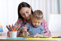 Mother and kid son drawing with colored pencils. Mother and child son drawing with colored pencils royalty free stock photos