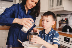 Mother and kid son preparing the dough for cookies and pouring flour Royalty Free Stock Photography