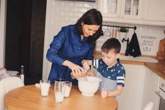 Mother and kid son preparing the dough for cookies and pouring flour Royalty Free Stock Photo