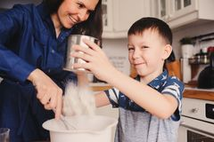 Mother and kid son preparing the dough for cookies and pouring flour Royalty Free Stock Image
