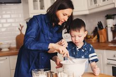 Mother and kid son preparing the dough for cookies and pouring flour Stock Photography