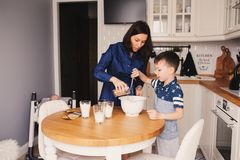 Mother and kid son preparing the dough for cookies and pouring flour Stock Photos