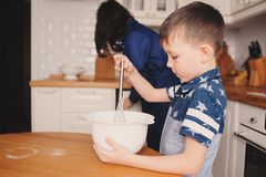 Mother and kid son preparing the dough for cookies and pouring flour Stock Images