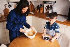 Mother and kid son preparing the dough for cookies and pouring flour Royalty Free Stock Photos