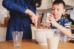 Mother and kid son preparing the dough for cookies and pouring flour Stock Image