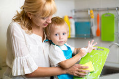 Mother And Kid Son Washing Dishes. Together Royalty Free Stock Photos