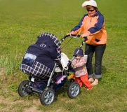 Mother and kid with stroller. Family of mother with kid carrying the stroller on the green lawn in holiday day Stock Photos