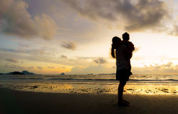 Mother and kid at sunset beach Royalty Free Stock Photo