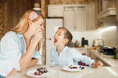Mother with kid tasting dessert and having fun royalty free stock image