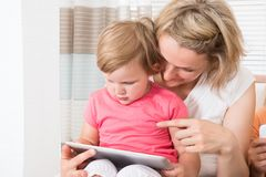 Mother and kid using tablet together Royalty Free Stock Photo
