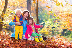 Mother and kids in autumn park. Mother and kids play in autumn park. Parent and children walk in the forest on a sunny fall day. Boy and girl playing outdoors royalty free stock photos