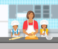 Mother with kids bake together at a kitchen Stock Image