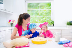 Mother and kids baking a pie. Young happy mother and her kids, adorable toddler girl and a little funny baby boy wearing pink and blue chef hats baking a pie Royalty Free Stock Photos