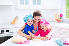 Mother and kids baking a pie. Young happy mother and her kids, adorable toddler girl and a little funny baby boy wearing pink and blue chef hats baking a pie Stock Photography