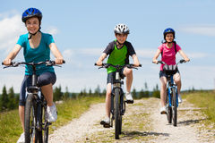 Family biking. Mother and kids biking in forest Royalty Free Stock Photos