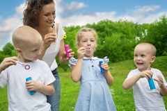 Mother with kids blowing bubbles Royalty Free Stock Photography