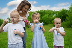 Mother with kids blowing bubbles Stock Photos