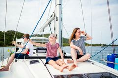 Family on board of sailing yacht. Mother and kids on board of sailing yacht having summer travel adventure stock photography