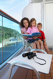 Mother, kids consider book on ship deck Stock Image