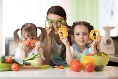 Mother and kids daughters having fun in the kitchen. Mother and her children having fun in the kitchen Royalty Free Stock Images