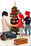 Mother with kids decorate tree. Back of mother with two kids decorate Christmas tree royalty free stock image