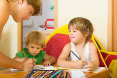 Mother and kids drawing with pencils Stock Photo
