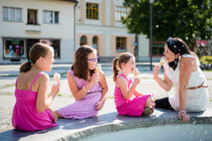 Mother with kids eating ice-cream outdoors royalty free stock photography