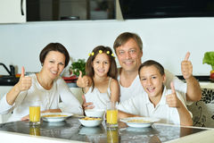 Mother with kids eating at table Royalty Free Stock Images