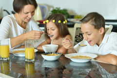 Mother with kids eating at table. Happy mother with kids eating at table royalty free stock photos
