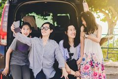 Mother and kids enjoy photograph when relax on car after long tr. Ip royalty free stock images
