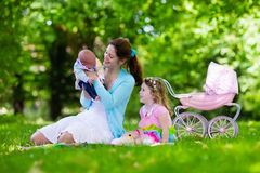 Mother and kids enjoying picnic outdoors. Family with children enjoying picnic outdoors. Mother with newborn baby and toddler child relax in a park. Little girl Stock Photography