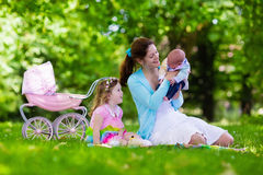 Mother and kids enjoying picnic outdoors. Family with children enjoying picnic outdoors. Mother with newborn baby and toddler child relax in a park. Little girl Stock Images