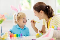 Mother and kids, family coloring Easter eggs. Mother and kids color Easter eggs. Face painting for little child. Little boy with bunny ears and mom dye eggs stock image