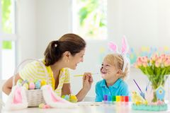 Mother and kids, family coloring Easter eggs. Mother and kids color Easter eggs. Face painting for little child. Little boy with bunny ears and mom dye eggs stock photo
