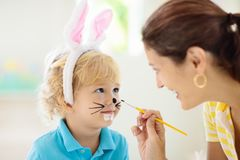 Mother and kids, family coloring Easter eggs. Mother and kids color Easter eggs. Face painting for little child. Little boy with bunny ears and mom dye eggs royalty free stock images