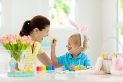 Mother and kids, family coloring Easter eggs. Mother and kids color Easter eggs. Face painting for little child. Little boy with bunny ears and mom dye eggs royalty free stock photography