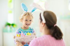 Mother and kids, family coloring Easter eggs. Mother and kids color Easter eggs. Little boy with bunny ears showing mom colorful candy eggs after Easter egg hunt royalty free stock photo