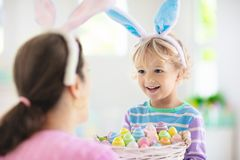 Mother and kids, family coloring Easter eggs. Mother and kids color Easter eggs. Little boy with bunny ears showing mom colorful candy eggs after Easter egg hunt stock photos