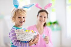 Mother and kids, family coloring Easter eggs. Mother and kids color Easter eggs. Little boy with bunny ears showing mom colorful candy eggs after Easter egg hunt royalty free stock images