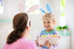 Mother and kids, family coloring Easter eggs. Mother and kids color Easter eggs. Little boy with bunny ears showing mom colorful candy eggs after Easter egg hunt royalty free stock image